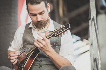 handsome big moustache hipster man playing mandolin