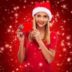 Beautiful santa woman holding gift box, red snowfall background