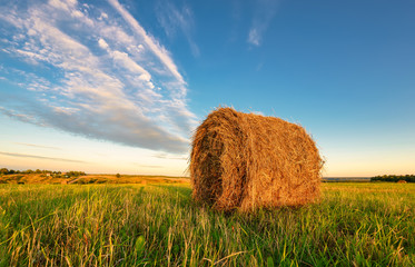 Haystack in the field under the blue sky.