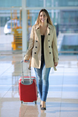 Traveler woman walking carrying a suitcase in an airport