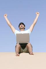 Mann sitzt im Sand mit Laptop
