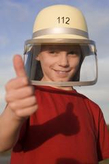 Junge trägt Helm, Daumen nach oben