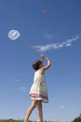 Mädchen versucht Schmetterlinge zu fangen, mit Netz