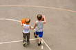 Two little boys playing on a basketball court