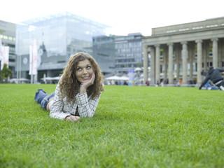 Deutschland, Stuttgart, junge Frau liegt im Gras