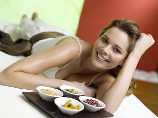 Frau liegt auf dem Bett mit Gewürzen in Schalen, lächeln