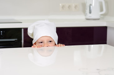 Cute little child in a chefs toque