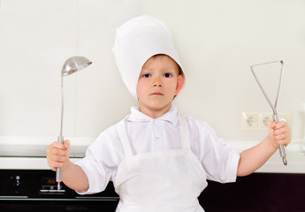 Proud little boy chef in a white toque