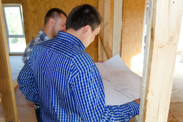 Two carpenters or builders discussing a plan