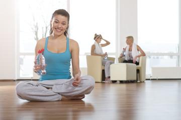 Deutschland, Frau mit Wasserflasche im Fitness-Studio