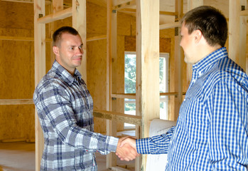 Two men shaking hands in a new build house