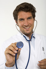 Männlicher Arzt hält Stethoskop, close-up, Portrait