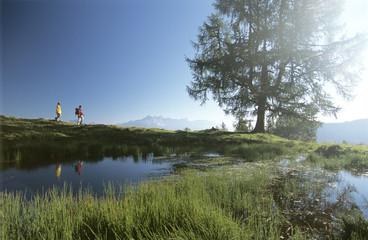 Österreich, Salzburger Land, zwei Menschen wandern durch die Berge