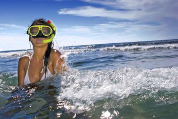 Frau trägt Schnorchel und Maske im Meer