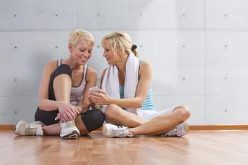 Deutschland, Freundinnen machen Pause im Fitnessstudio und zeigen etwas auf Smartphone