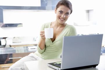Frau sitzen in der Küche, mit Laptop, halten Tasse