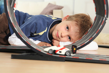 junge spielt mit Spielzeugauto Carrerabahn