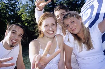Vier junge Leute zeigen Victory Zeichen, close-up, Portrait