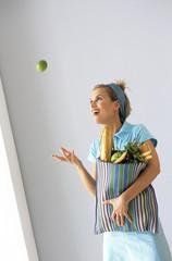 Frau mit Einkaufstasche wirft Apfel in die Luft