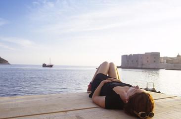 Kroatien, Dubrovnik, Frau liegt auf Pier