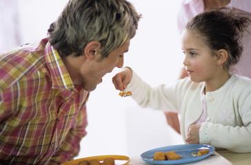 Mädchen füttert Vater mit Fischstäbchen