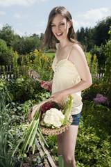 Deutschland, Bayern, Frau jung halten Korb mit Gemüse im Garten, Lächeln, Portrait