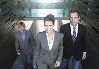 Deutschland, Köln, Drei Geschäftsleute im Treppenhaus