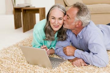 Paar liegen auf dem Teppich mit Laptop, Mann küssen Frau