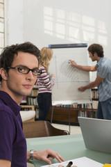 Junger Mann erklärt Frau Diagramm, auf Mann lächeln konzentrieren