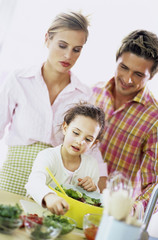 Eltern beobachten Tochter bei der Salatzubereitung