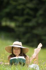 Junge Frau mit Buch, liegend in der Wiese