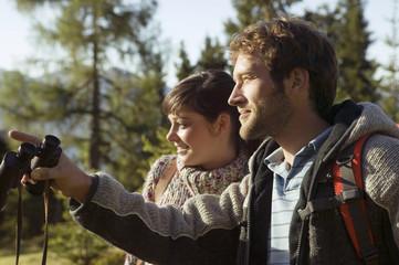 Junges Paar beim Wandern, Mann mit Fernglas