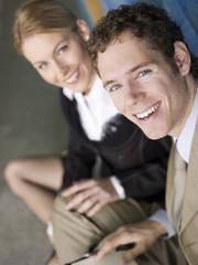 Geschäftsfrau und Mann sitzen lächeln, close-up, Portrait