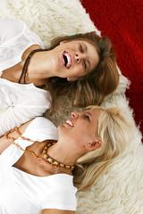Zwei lachende Frauen auf dem Boden