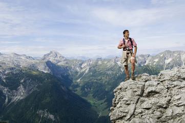 Österreich, Salzburger Land, junger Mann auf Bergspitze