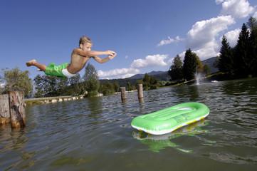 Junge springt in den See