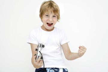 Kleiner Junge mit Joystick, jubelt und ballt die Fäuste