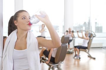 Deutschland, Frau trinkt Wasser im Fitness-Studio