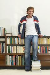Junger Mann stehen vor Bücherregal, Füße auf Bücher, Portrait