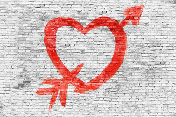 Heart with arrow painted over brick wall