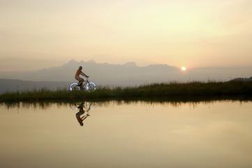 Österreich, Alpen, Frau fährt Fahrrad am See