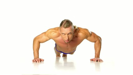 Handsome muscular man doing push-up on white background