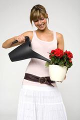 Frau jung gießen Blumen, lächeln, close-up