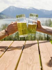 Deutschland, Bayern, Tegernsee, zwei Männer prosten mit Biergläsern
