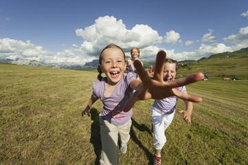 Italien, Seiseralm, Mutter und Töchter, in Wiese laufen, lachen, Porträt