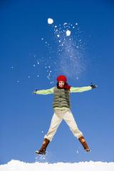 Österreich, Mädchen springen im Schnee mit Arme ausstrecken, Porträt,