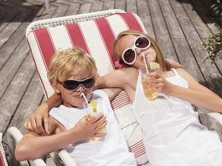 Bruder und Schwester liegen in Liegestühlen, trinken Saft