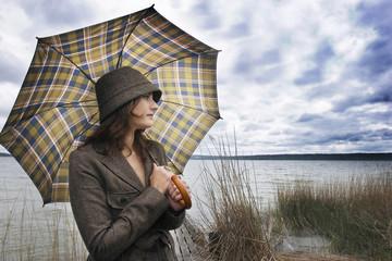 Junge Frau mit Regenschirm, Wegschauend