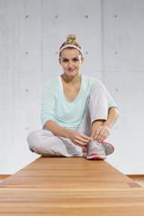 Deutschland, Frau macht Pause in der Turnhalle, lächelnd