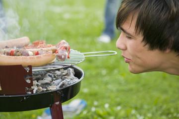 Junger Mann am Grill mit Fleisch, Seitenansicht